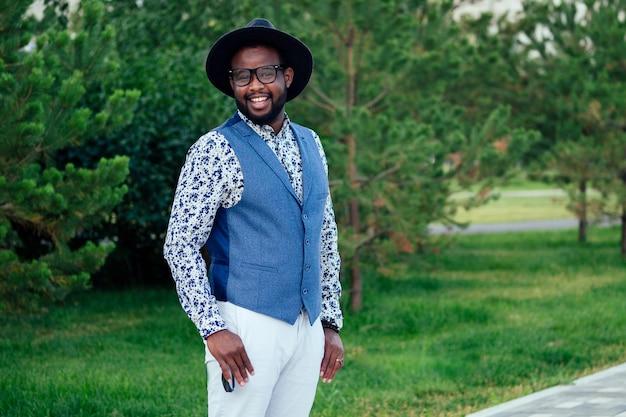 여름 공원에서 세련된 정장 흰색 바지와 검은 모자를 쓴 젊고 잘 생긴 세련된 모델 아프리카계 미국인 남자. 라틴계 미국인 히스패닉 사업가 흑인 남자가 사진 촬영에서 포즈를 취하고 있습니다.