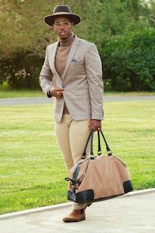 여름 공원에서 세련된 양복을 입은 젊고 잘 생긴 세련된 재단사 모델 아프리카계 미국인 남자. 라틴계 미국인 히스패닉 사업가 흑인 남자가 사무실에서 퇴근 후 걷고 있습니다.