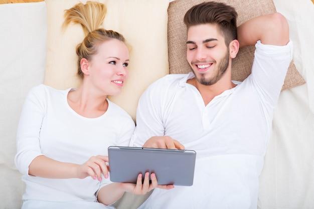 Молодая и счастливая пара с планшетным пк в постели сверху.