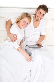 Молодая и счастливая пара с планшетным пк в постели.
