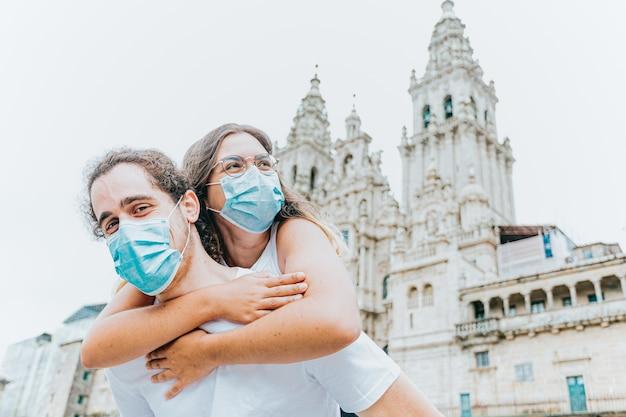 旅行中に古代の大聖堂の前に置かれたマスクを持つ若くて幸せなカップル