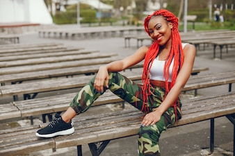 A young and stylish dark-skinned girl with red dreads sitting in the summer park