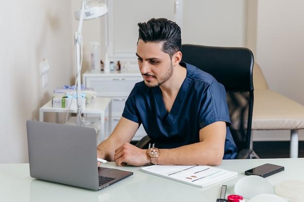 Молодой арабский или турецкий врач в синей форме проводит онлайн-консультации
