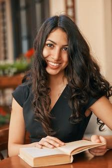 カフェで本を読んでいる若いアラビア人女性