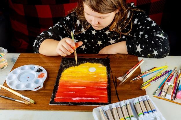 若い芸術家が油絵の具でキャンバスに夕日を描きます。