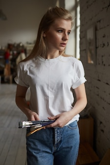 Молодой художник стоит в живописной мастерской с кистями