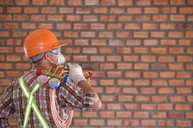 若いアジアのエアコン技術者またはエアコン設置技術者が家や建物のエアコンを修理しようとしています。エアコン修理業者は家のユニットで働いています。