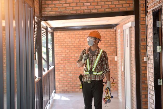 若いアジアのエアコン技術者またはエアコン設置技術者がエアコンを修理しようとしています
