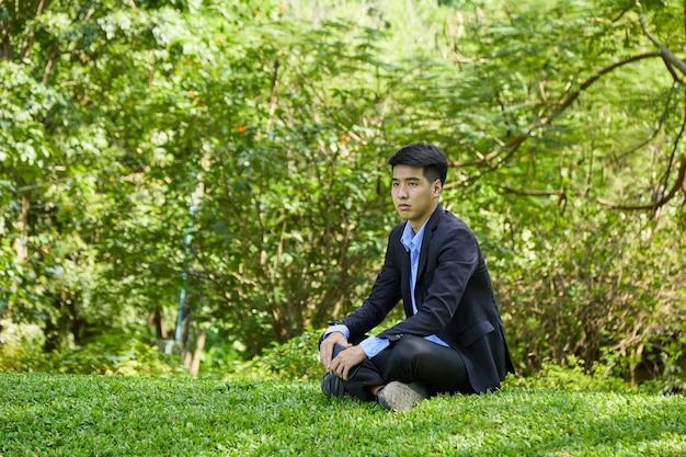 Молодой азиатский бизнесмен отдыхает в природном парке