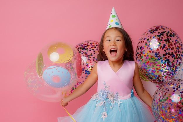 Молодая азиатская девушка на дне рождения играет с воздушными шарами на розовом