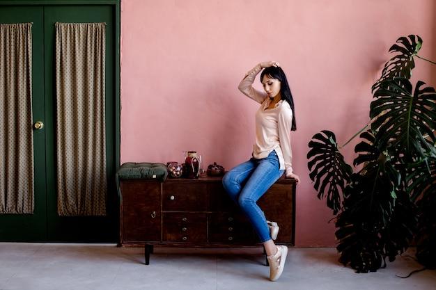 Молодая азиатская девушка сидит на тумбочке на розовой бетонной стене.