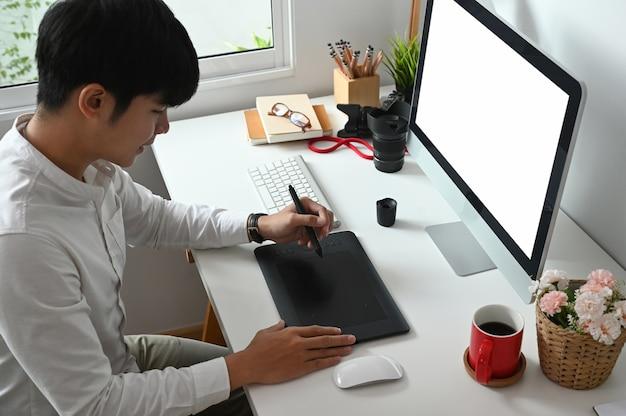 Молодой азиатский графический дизайнер работает над компьютером и графическим планшетом в офисе