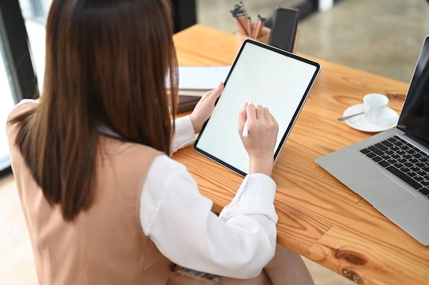 Молодой азиатский графический дизайнер работает над компьютерным планшетом с пустым экраном на деревянном столе