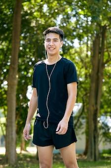 Молодой азиатский счастливый веселый улыбающийся человек во время утренней пробежки на открытом воздухе. фитнес, спорт, упражнения кроссфит и концепция тренировки.