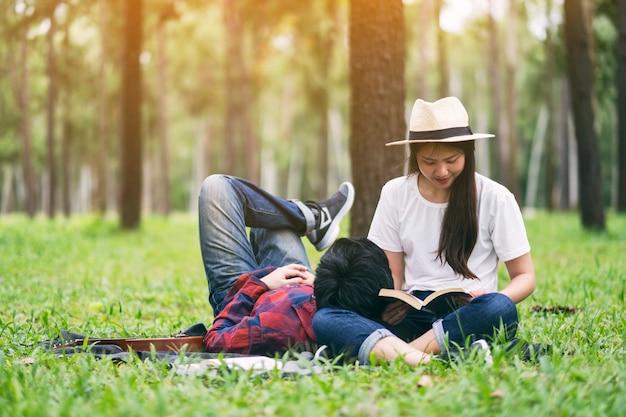 Молодая азиатская пара любовника читает книгу и вместе ложится в парке