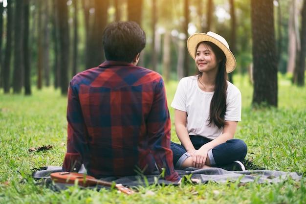 公園で一緒に座っている若いアジアの恋人のカップル
