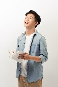 青いシャツに立って、本を持って読書をし、白い背景のために隔離された若いアジア人男性。