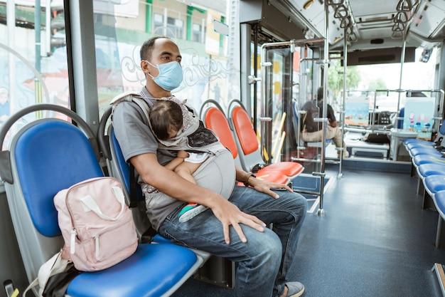 마스크를 쓰고 젊은 아시아 남자는 여행하는 동안 버스에서 자고있는 작은 아기 소녀를 들고 벤치에 앉아있다.