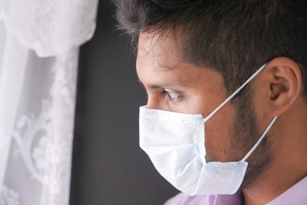 Молодой азиатский мужчина с защитной маской на лице грустит