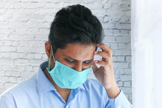 Молодой азиатский человек с защитной маской в лице грустно