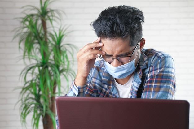悲しい感じの顔に保護マスクを持つ若いアジア人