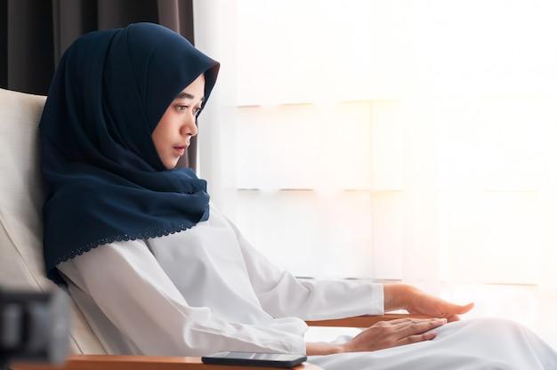 ダークブルーのヒジャーブとクロスオーバーのスカーフを身に着けている若いアジアのイスラム教徒の女性。将来のビジネスを真剣に考え、決断するためのマーケティングと近代化の着席と思考と計画