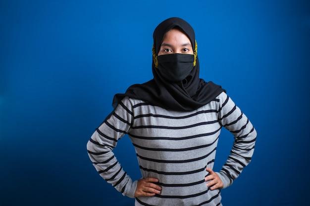 코로나 바이러스 질병의 확산을 막는 의료용 안면 마스크를 쓴 젊은 아시아 학생. 파란색 배경에 얼굴에 수술용 마스크를 쓴 남자의 클로즈업