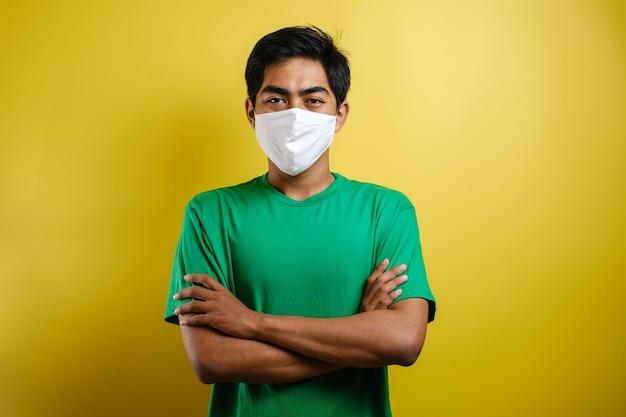 コロナウイルス感染症の蔓延を防ぐ医療用フェイスマスクを着用した若いアジア人学生。黄色の背景に対して彼の顔にサージカルマスクを持つ男のクローズアップ