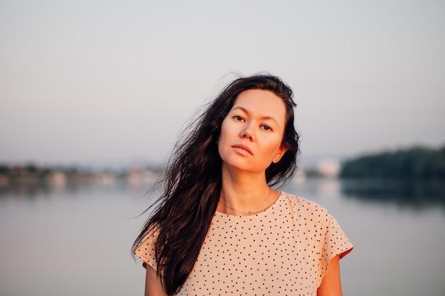 シルク水玉ドレススタンの若い美しい女性の日没のクローズアップの肖像画で若いアジアの女性...