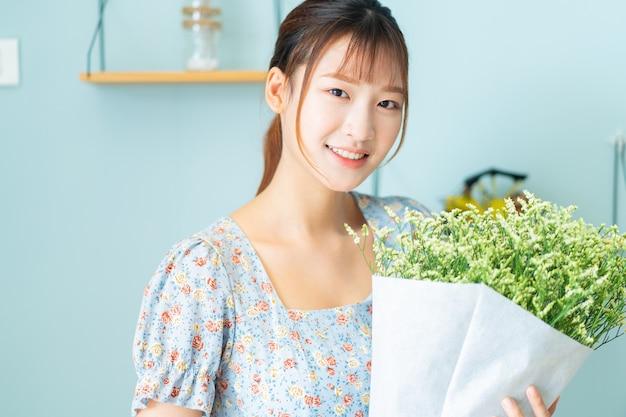 彼女の部屋に花を持っている若いアジアの女性