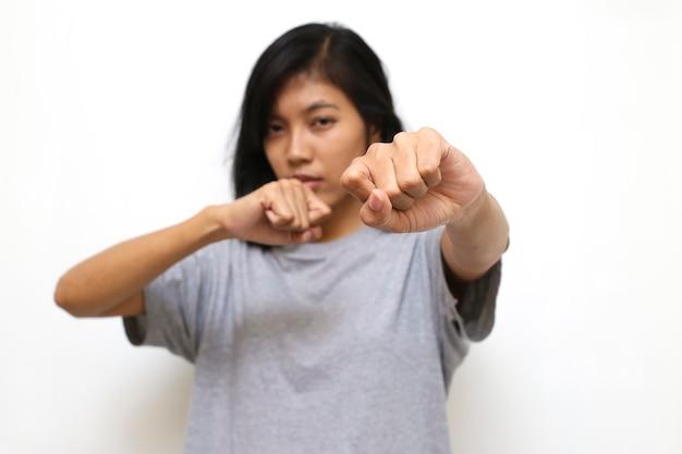 Молодая азиатская женщина показывает ее кулак в белом пространстве