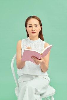 座って、青い背景の上に分離された彼女のメモを書いている若いアジアの女性