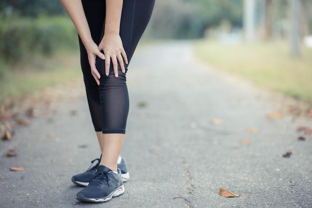У молодой азиатской женщины болят колени после бега.
