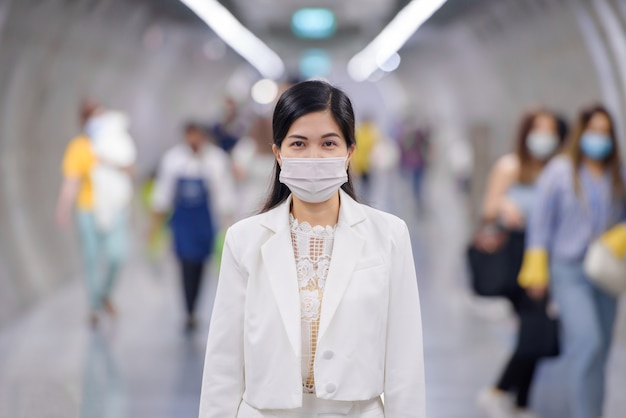 신종 코로나 바이러스에 대한 마스크를 쓴 젊은 아시아 여성이 공공 기차역에서 군중 속을 걷고있다.