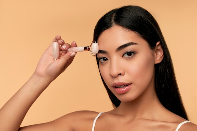 きれいな輝く肌の若いアジア人女性が、ベージュの壁にクォーツローラーを使ってフェイシャルマッサージをします。