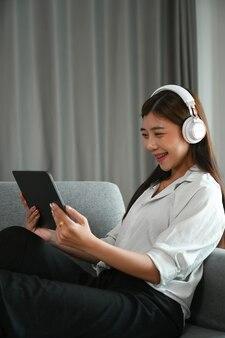 時間を楽しんで、リビングルームでタブレットでリラックスしてソファに座っているヘッドフォンを持つ若いアジアの女性。