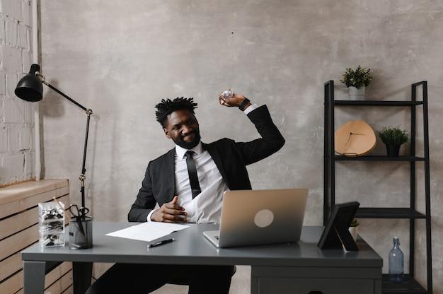젊은 야심 찬 아프리카 계 미국인 투자자가 컴퓨터에서 일하며 증권 시장을 분석합니다.