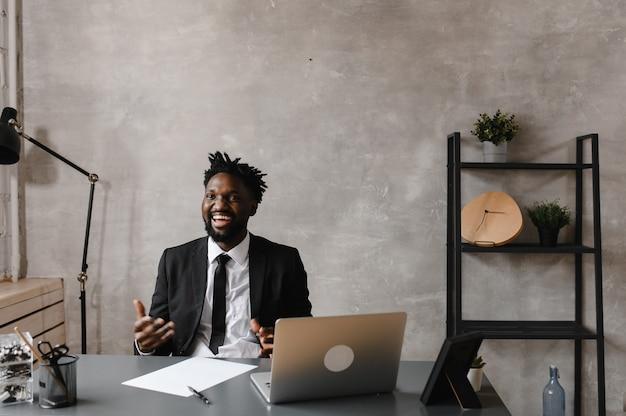 젊은 야심 찬 아프리카 계 미국인 투자자가 컴퓨터에서 일합니다.