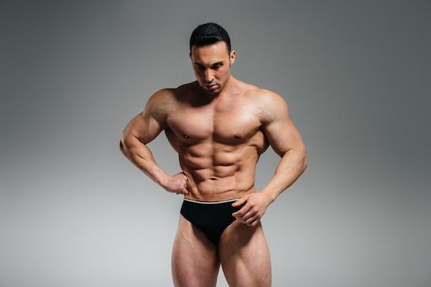 젊은 운동 선수 보디 빌더는 스튜디오에서 토플리스로 포즈를 취하고 복근과 근육을 과시합니다.