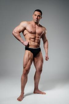 若いアスリートのボディービルダーがトップレスでスタジオでポーズをとり、腹筋と筋肉を披露します