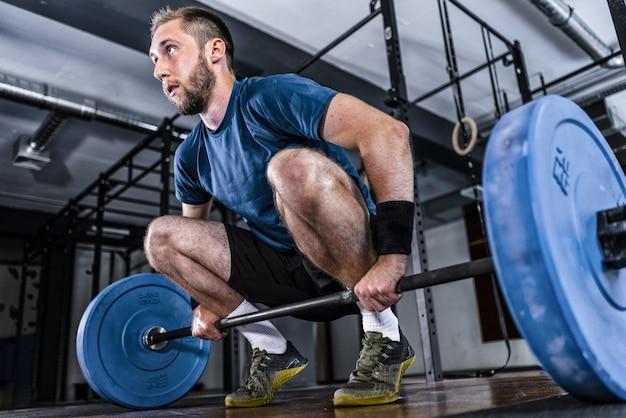Молодой спортсмен занимается тяжелой атлетикой в тренажерном зале