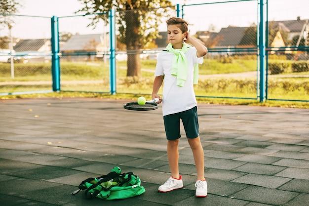 若いアスリートがボールを乗せたテニスラケットを持っています。テニスプレーヤーはトレーニング前にウォームアップします