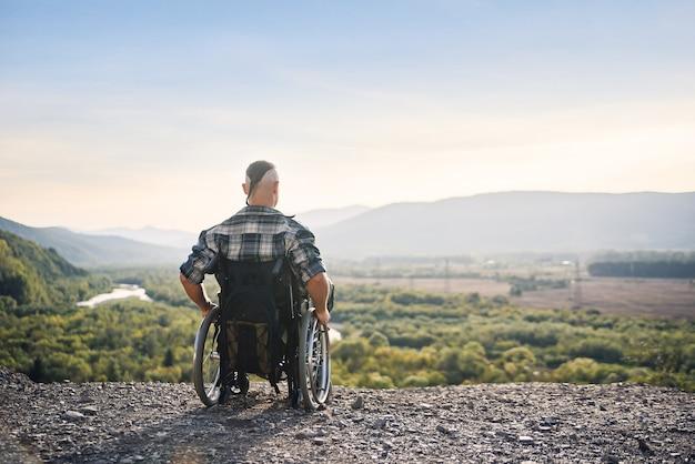 若いアスリートは、山の新鮮な空気を楽しんでいる車椅子で一時的に障害を負っています。
