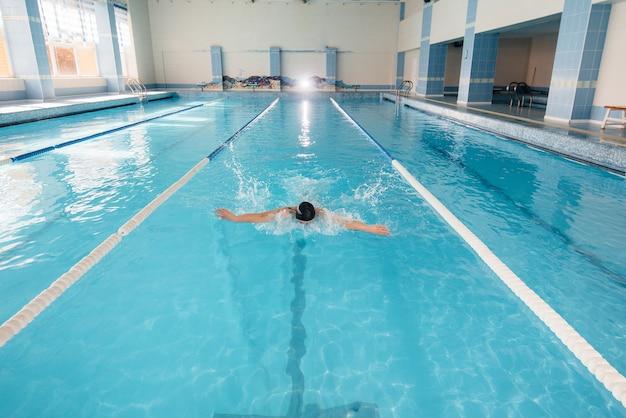 Юный спортсмен тренируется и готовится к соревнованиям по плаванию в бассейне. здоровый образ жизни.