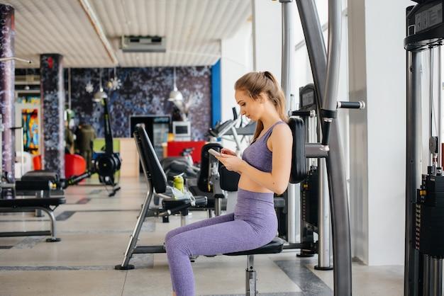 Молодая спортсменка пользуется телефоном в тренажерном зале и делает селфи.