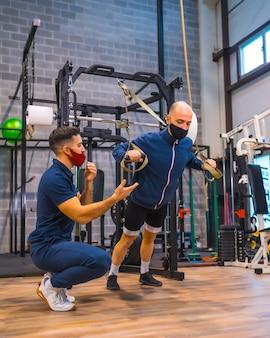 코로나 바이러스 전염병에서 스트립으로 운동을하는 체육관에서 강사와 함께 젊은 운동 선수