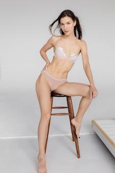 白い下着で隔離された壁の若い運動とフィットの女の子フィットネス下着の広告の概念