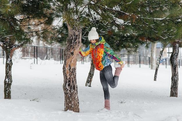 Молодая спортивная девушка разминается перед бегом в морозный день. фитнес, бег.