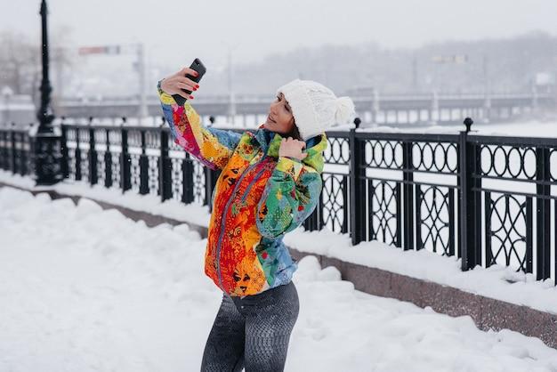 체육 소녀가 서리가 내린 눈이 내리는 날에 셀카를 찍습니다. 피트니스, 레크리에이션.