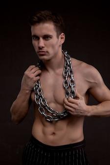 맨몸에 쇠사슬을 매고 있는 젊은 운동선수. 어두운 배경의 사진